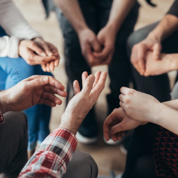 Close-up of hands of people sitting in a circle during a therapy group meeting