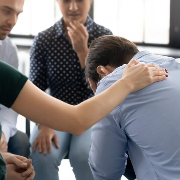 During group therapy session participants supporting crying desperate guy, provide psychological assistance talking encouraging words share mental pain try to help, struggle with addictions treatment